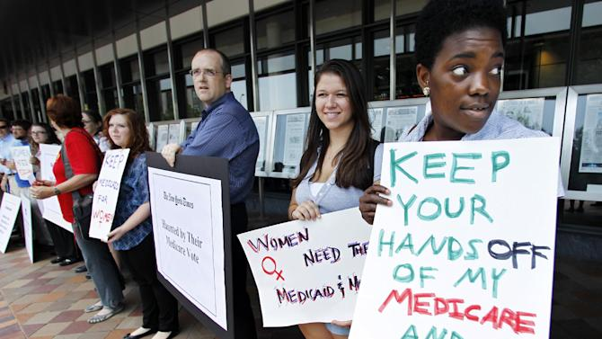 FILE - In this June 13, 2011, file photo Dena Robinson, from right, and Hannah Hoffman, join dozens of Medicare advocates gathered outside the Newseum in Washington. Democrats are hitting the reset button on health care for next year's elections. Weary of getting pounded over the new health overhaul law, President Barack Obama and his party are changing the subject to Medicare. Obama signaled last week he's on board with the shift. (AP Photo/Manuel Balce Ceneta, File)