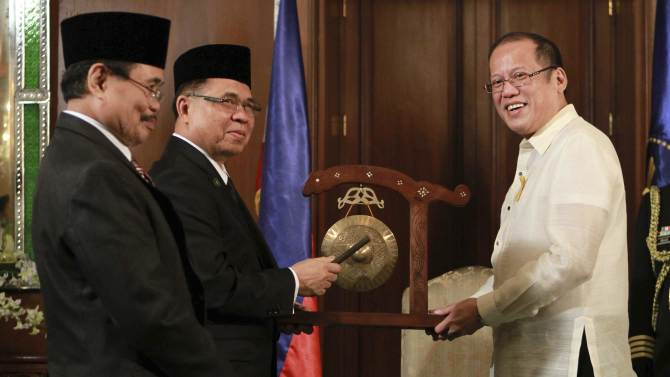 Philippine President Benigno Aquino III, right, receives a gong from Moro Islamic Liberation Front (MILF) Chairman Al Haj Murad, center, and MILF Peace Panel chief Mohagher Iqbal, left, before the historic signing of the framework agreement between the Philippine government and the MILF at the Malacanang Presidential Palace in Manila, Philippines, on Monday Oct. 15, 2012. Muslim rebels and the Philippine government overcame decades of bitter hostilities and took their first tentative step toward ending one of Asia's longest-running insurgencies with the ceremonial signing of a preliminary peace pact Monday that both sides said presented both a hope and a challenge. (AP Photo/Rouelle Umali, Pool)