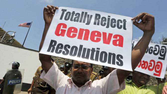 A Sri Lankan government supporter holds a placard during a protest outside the U.S. Embassy against a United States-sponsored draft resolution discussed at the United Nations Human Rights Council in Geneva, Thursday, March 21, 2013, in Colombo, Sri Lanka. The resolution, if carried out, is expected to urge Sri Lanka to investigate allegations of serious human rights violations in the country's civil war. The protesters call it an interference in the country's domestic affairs. (AP Photo/Eranga Jayawardena)