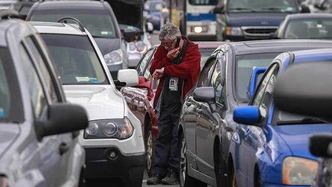 A man looks at his watch while waiting for hours to get fuel from a gas station in the New York City borough of Queens