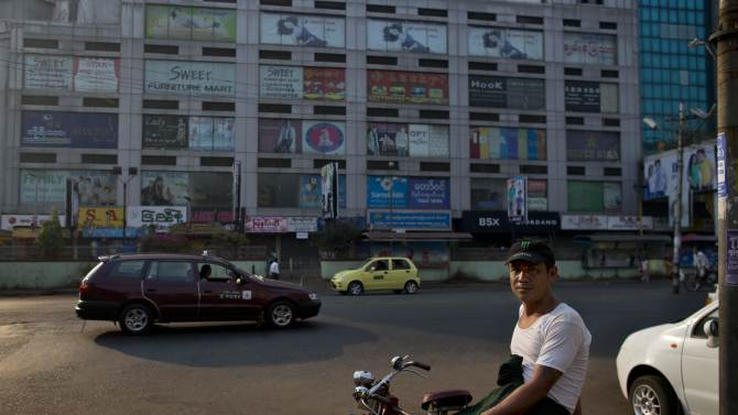 A rickshaw man rests outside a popular shopping mall, that was shout down early on Monday due to the fear of spreading sectarian clashes in Yangon, Myanmar, Tuesday, March 26, 2013. Myanmar's government warned Monday that religious violence could threaten democratic reforms after anti-Muslim mobs rampaged through three more towns in the country's predominantly Buddhist heartland. The mobs destroyed mosques and burned dozens of homes over the weekend despite attempts by the government to stem the nation's latest outbreak of sectarian violence. (AP Photo/Gemunu Amarasinghe)