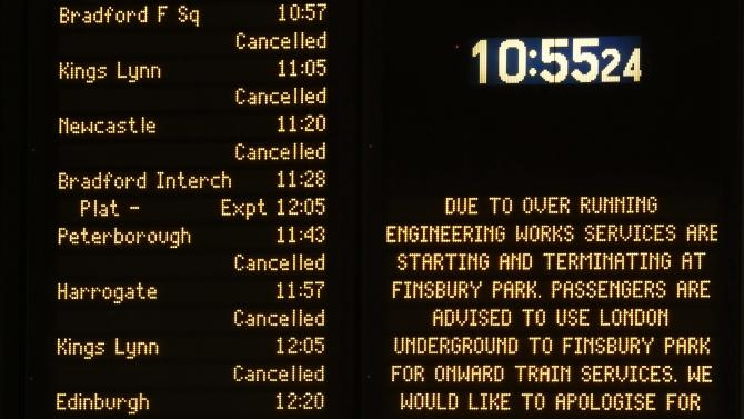 An illuminated information board is seen at King's Cross Station in London