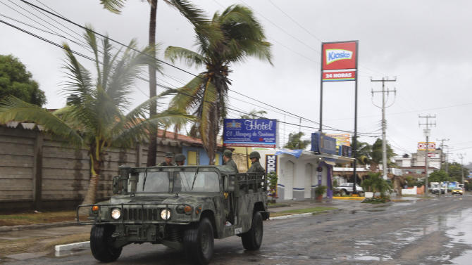 A navy vehicle drives along a street in the coastal town of Barra de Navidad as the community prepares for the arrival of Hurricane Bud along the Pacific coast of Mexico, Friday, May 25, 2012. Hurricane Bud lost a little of its sting early Friday, but remained a potent Category 2 storm as it headed toward a string of laid-back beach resorts and small mountain villages on Mexico's Pacific coast south of Puerto Vallarta. (AP Photo/Bruno Gonzalez)