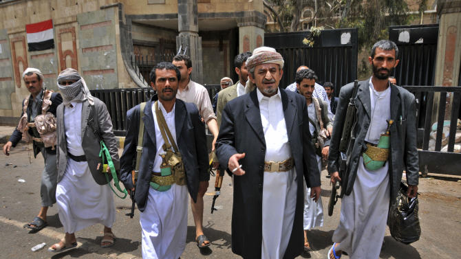 The head of the powerful Hashid tribe, Sheik Sadeq al-Ahmar, center, walks with his body guards near his house in Sanaa, Yemen, Thursday, May 26, 2011. Yemen's government said 28 people were killed in an explosion at a weapons storage site Thursday, but the opposition claimed military forces shelled a building used by tribal fighters who have risen up against President Ali Abdullah Saleh and warn of civil war if he refuses to step down. (AP Photo/Mohammed Al-Sayaghi)
