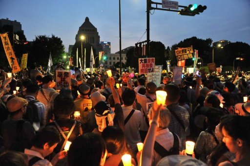 Protesters hold lit candles and placards as they take part in a rally in front of Japan's parliament