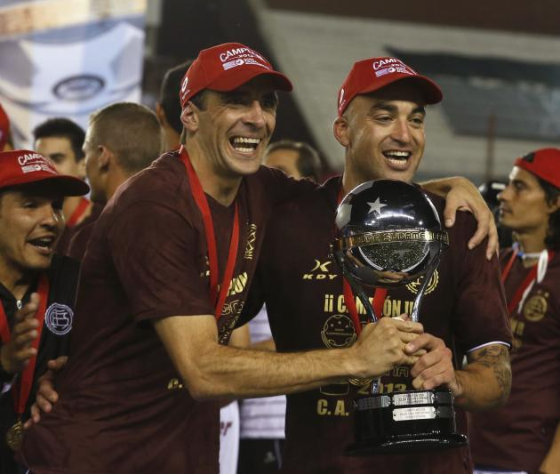 Somoza and Silva of Argentina's Lanus soccer celebrate with trophy after Lanus defeated Brazil's Ponte Preta in final Copa Sudamericana match in Buenos Aires