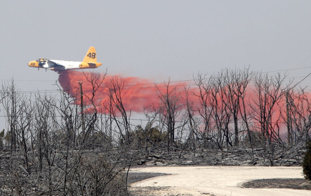 An air tanker drops fire retardant on a hot spot in an area destroyed by a wildfire at Possum Kingdom Lake, Texas, Wednesday, Aug. 31, 2011. (AP Photo/LM Otero)