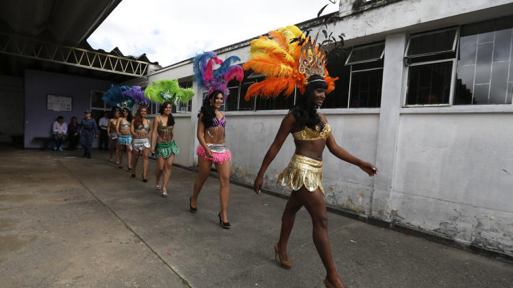 Inmates in costume walk to the stage to participate in a beauty pageant inside El Buen Pastor women's prison in Bogota, Colombia, Friday, Sept. 27, 2013. The contest is held every September to honor the Virgin of Mercedes, the patron saint of prisons. (AP Photo/Fernando Vergara)