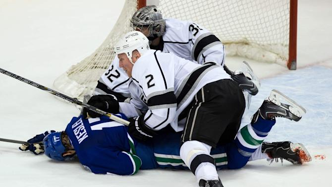 Los Angeles Kings' Matt Greene (2) sports a blood soaked right sock as he checks Vancouver Canucks' Ryan Kesler during the third period of an NHL hockey game Saturday, April 5, 2014, in Vancouver, British Columbia. Vancouver won 2-1