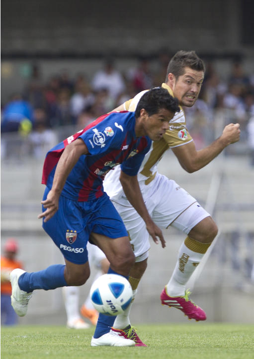 Atlante's Salustiano Candia, front, controls the ball under pressure from Pumas' Dante Lopez at a Mexican soccer league match in Mexico City, Sunday, March 16, 2014