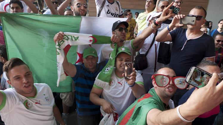A group of Algeria supporters take a selfie as they sing and hold Algerian flags the day before their team's group H match against Belgium, during the 2014 soccer World Cup in Belo Horizonte, Brazil, Monday, June 16, 2014