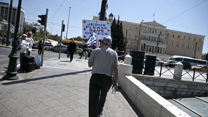 A man holding a Greek national flag and a placard makes his way on the main Constitution Square as the parliament building is seen in Athens
