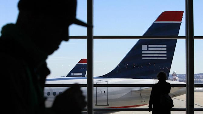 FILE - In this Sunday Dec. 27, 2009 file photo, passengers walk past US Airways planes at Reagan National Airport in Washington. It will be several months, if not years, before passengers see any significant impact from the American-US Airways merger. (AP Photo/Jacquelyn Martin, File)