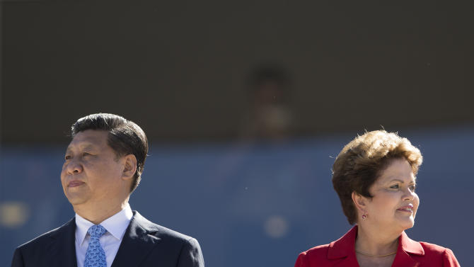 Brazil's President Dilma Rousseff, right, attends a welcoming ceremony for China's President Xi Jinping before signing agreements at Planalto presidential palace in Brasilia, Brazil, Thursday, July 17, 2014. Rousseff says the agreements show that ties between China and Brazil have never been stronger. In 2009, China pushed the U.S. aside to become Brazil's biggest trading partner, and the deals signed today cover a wide spectrum of sectors, including aviation, railways, mining, education and construction. (AP Photo/Felipe Dana)