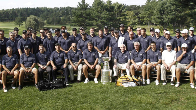 Current and former Boston Bruins players and management pose for a photo with the Stanley Cup during the Boston Bruins Foundation golf tournament at The International Golf Club in Bolton, Mass., Monday, Sept. 12, 2011. (AP Photo/Winslow Townson)