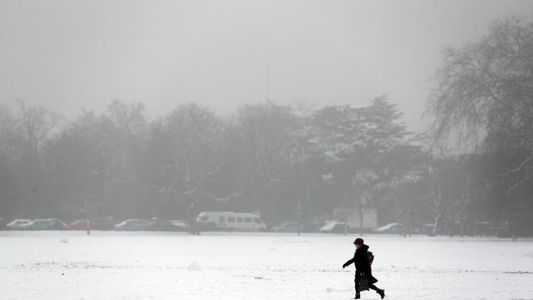 A woman walks in a park covered in snow in west London, Tuesday, Jan. 22, 2013. Cold weather continues to grip large parts of Britain. (AP Photo/Lefteris Pitarakis)