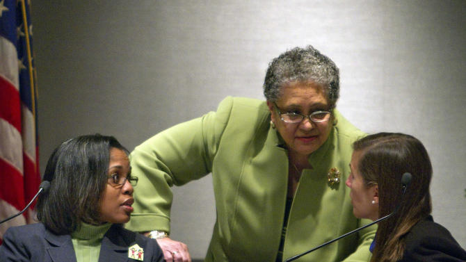 FILE In this photo taken Jan. 18, 2011 Atlanta Public Schools Superintendent Dr. Beverly Hall, center, speaks with school board member LaChandra Butler Parks, left, and Cecily Harsch-Kinnane, vice chair of the board, right, during the city's specially called public school board meeting  in Atlanta.  A new state report reveals how far some Atlanta public schools went to raise test scores in the nation's largest-ever cheating scandal.  The scandal first came to light two years ago. Now, investigators have concluded that nearly half the city's schools allowed cheating to go unchecked for as long as a decade, beginning in 2001. (AP Photo/David Goldman)