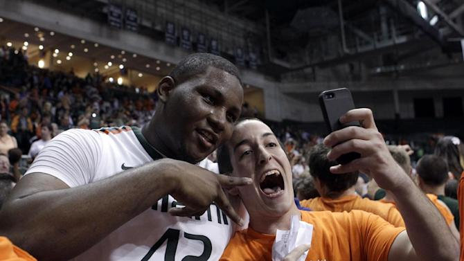 A fan takes a picture with Miami's Reggie Johnson (42) after a 90-63 win against Duke at an NCAA college basketball game in Coral Gables, Fla., Wednesday, Jan. 23, 2013. (AP Photo/Alan Diaz)