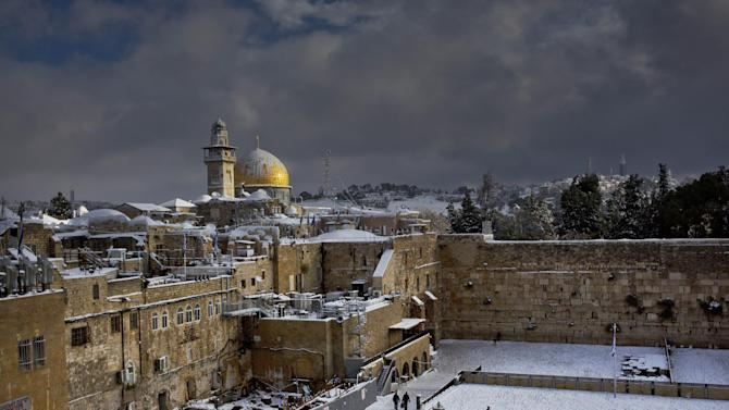 File - In this Dec. 13, 2013 file photo, the Western Wall, right, and the gilded Dome of the Rock, among the holiest sites for Jews and Muslims, are covered in snow. Israeli police stormed a sensitive holy site in Jerusalem on Wednesday, April 16, 2014, firing tear gas to disperse a protest by Palestinian Muslim worshippers, officials said. Police spokesman Micky Rosenfeld said the crowd hurled stones and firecrackers from atop the compound known to Jews as the Temple Mount, the holiest site in Judaism. (AP Photo/Dusan Vranic, File)