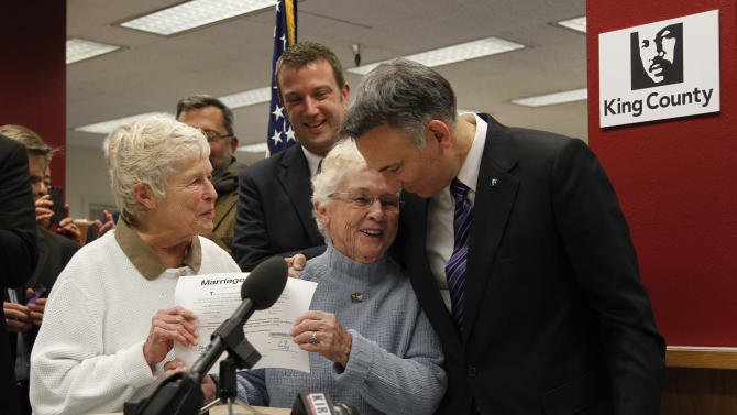 King County Executive Dow Constantine, right, leans down to embrace Pete-e Petersen as her partner, Jane Abbott Lighty, watches after Constantine issued them the first marriage license to a same-sex couples, Thursday, Dec. 6, 2012, in Seattle. Constantine began issuing the licenses immediately upon certification of the November election that passed Referendum 74. (AP Photo/Elaine Thompson)