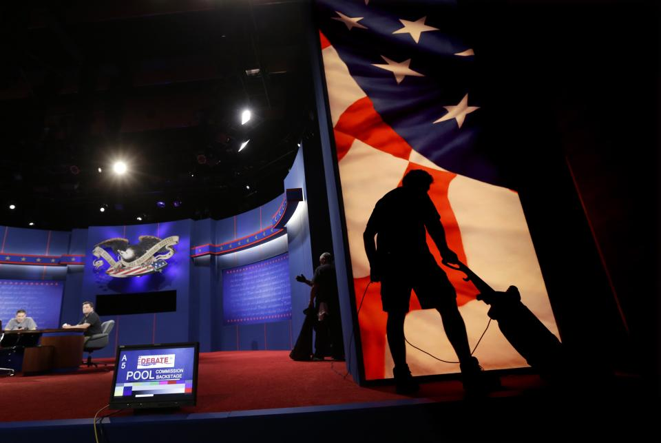 A worker vacuums as the set for Monday's presidential debate is prepared, Sunday, Oct. 21, 2012, in Boca Raton, Florida. President Barack Obama and Republican presidential candidate and former Massachusetts Gov. Mitt Romney will hold their final debate Monday. (AP Photo/Eric Gay)