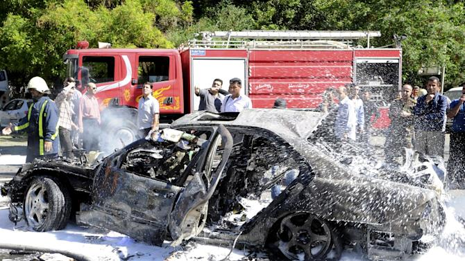 This photo released by the Syrian official news agency SANA, shows Syrian fire fighters extinguishing burning cars after a car bomb exploded in the capital's western neighborhood of Mazzeh, in Damascus, Syria, Monday, April. 29, 2013. State-run Syrian TV says the country's prime minister has escaped an assassination attempt when a bomb went off near his convoy. Syrian TV says Prime Minister Wael al-Halqi was unhurt in the attack in the capital's western neighborhood of Mazzeh. (AP Photo/SANA)