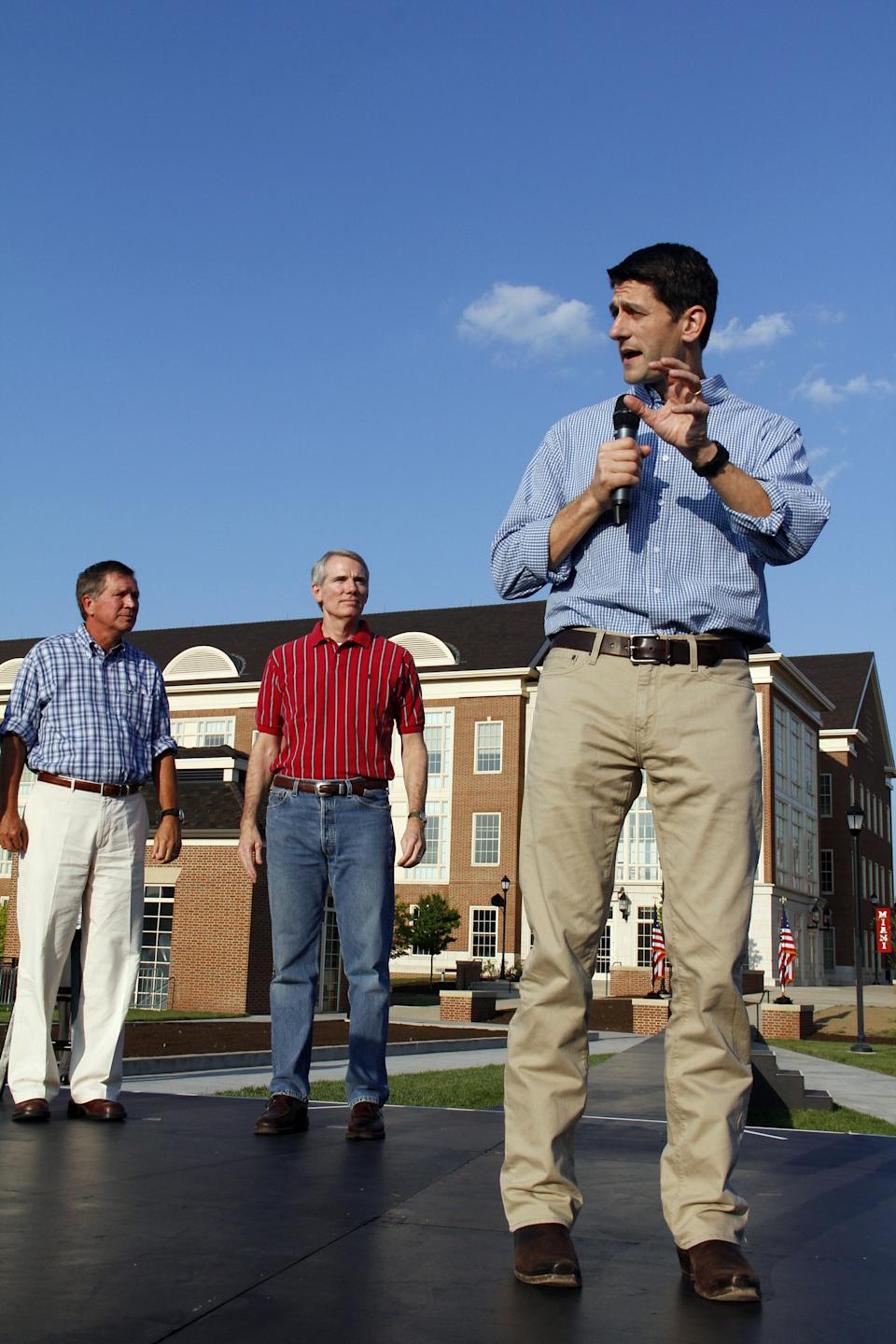 Vice Presidential candidate Rep Paul Ryan, R-Wis., right, talks to supporters at a rally on the campus of Miami University in Oxford Ohio, Wednesday Aug. 15, 2012, as Ohio Gov. John Kasich, left, and Rep. Rob Portman, listen. (AP Photo/Tom Uhlman)