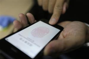 File photo of a journalist testing the new iPhone 5S Touch ID fingerprint recognition feature in Beijing