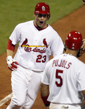 St. Louis Cardinals' David Freese (23) celebrates as he is met at home by Albert Pujols after hitting a three-run home run during the seventh inning of a baseball game against the New York Mets on Wednesday, Sept. 21, 2011, in St. Louis. (AP Photo/Jeff Roberson)
