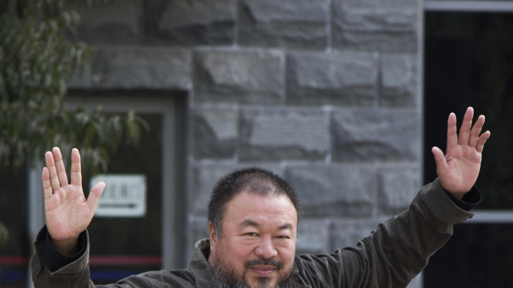 Chinese Activist artist Ai Weiwei waves to the journalists before he enter the Beijing No. 2 People's Intermediate Court for his appeal in Beijing Thursday, Sept. 27, 2012. Chinese authorities on Thursday rejected Ai's second appeal of a $2.4 million tax fine, meaning his design company will have to pay the penalty. (AP Photo/Andy Wong)