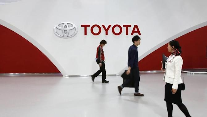 Employees and customer walk in front of Toyota Motor's logo at the company's showroom in Tokyo