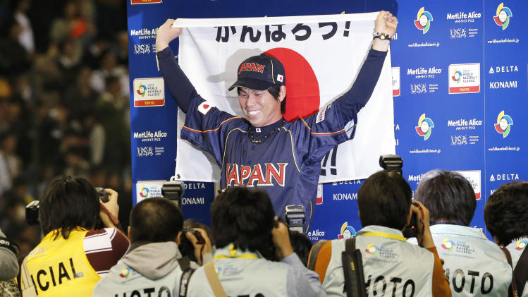 Japan's starter Kenta Maeda poses with a Japanese flag for photographers after beating the Netherlands in their World Baseball Classic second round game at Tokyo Dome in Tokyo, Sunday, March 10, 2013. The game was called in the bottom of the seventh inning with a score of 16-4. (AP Photo/Koji Sasahara)
