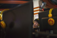 A man uses a computer at an internet cafe in central Beijing, China, Friday, Dec. 28, 2012. China's new communist leaders are increasing already tight controls on Internet use and electronic publishing following a spate of embarrassing online reports about official abuses. (AP Photo/Alexander F. Yuan)