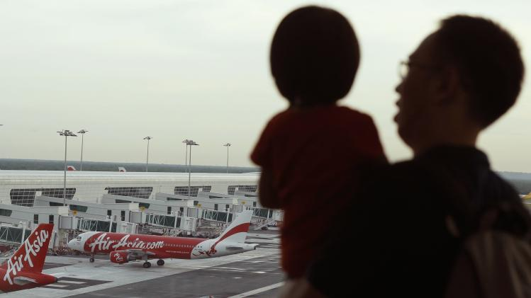 A man and his daughter look at AirAsia planes at Kuala Lumpur International Airport