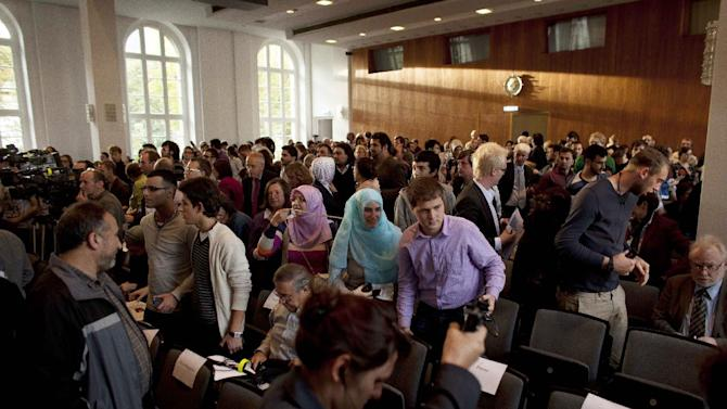 People leave the main hall of the Humboldt University after police call to evacuate the room immediately minutes prior to a speech of Turkish President Abdullah Gul in Berlin, Monday, Sept. 19, 2011. Berlin police are clearing a university where Turkish President Abdullah Gul was due to speak after a German news agency reported a bomb threat. (AP Photo/Markus Schreiber)