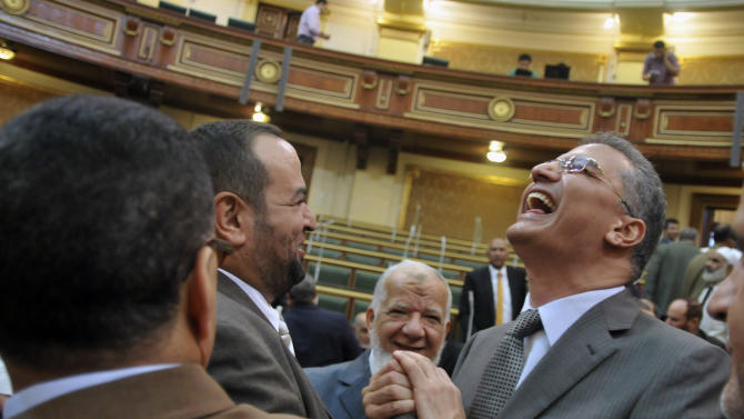 Egyptian lawmakers greet each other at a brief session of Parliament, the first since the country's high court ruled the chamber unconstitutional, in Cairo, Egypt, Tuesday, July 10, 2012. Egypt's Islamist-dominated parliament convened Tuesday in defiance of a ruling by the country's highest court and swiftly voted to seek a legal opinion on the decision that invalidated the chamber over apparent election irregularities. (AP Photo)