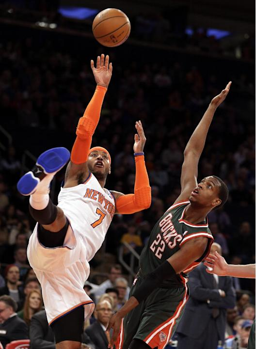New York Knicks' Carmelo Anthony, left, shoots the ball against Milwaukee Bucks' Khris Middleton in the first quarter of an NBA basketball game at New York's Madison Square Garden, Saturda