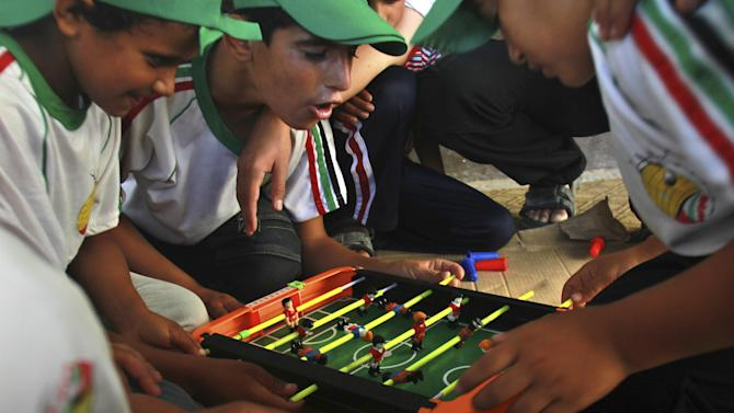 In this Wednesday, July 11, 2012 photo, Palestinian boys play table football at a summer camp run by Hamas inside a school in Al-Qarara near Khan Younis, southern Gaza Strip. Since taking over Gaza five years ago, Hamas has competed with a U.N. agency for the hearts of Palestinian children. Each side ran summer camps, with Hamas featuring lessons in Islam and political indoctrination and the U.N. offering sports and games. Hamas has now won by default _ the U.N. canceled its camps this year because of a drop in donations.(AP Photo/Adel Hana)