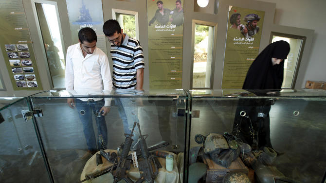 In this picture taken on Friday May 21, 2010, Lebanese citizens look at war booty captured by Hezbollah from Israeli troops, during the inauguration of a Hezbollah war museum, in Mlita Village, southern Lebanon. Hezbollah may have suffered setbacks from Syria's civil war, with many Lebanese angry over its backing of President Bashar Assad's regime. But that's unlikely to cost the Shiite militant movement its powerful grip in Lebanon, observers say. The group's overwhelming arsenal is still the foundation of its strength, bolstered by political alliances. (AP Photo/Hussein Malla)