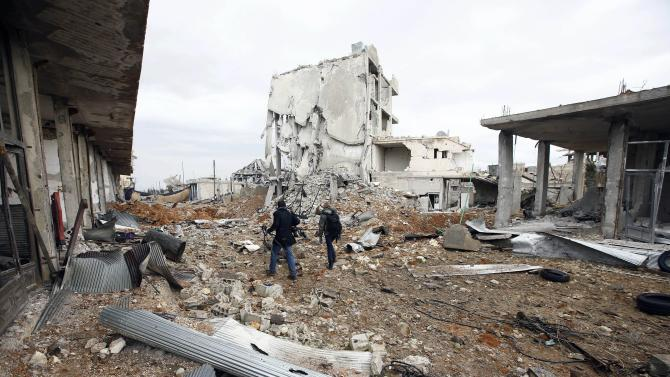 Visiting journalists walk between damaged buildings in the northern Syrian town of Kobani