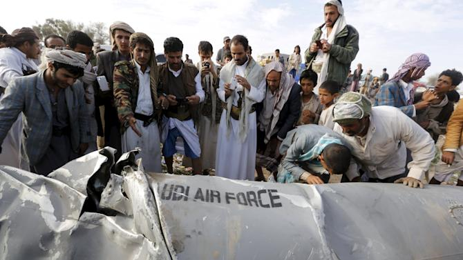 People check a part of a Saudi fighter jet found in Bani Harith district north of Yemen's capital Sanaa