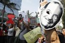 People protest holding masks of Mexican telecommunications tycoon Slim as he attends Meeting of Latin American Businessmen in Lima