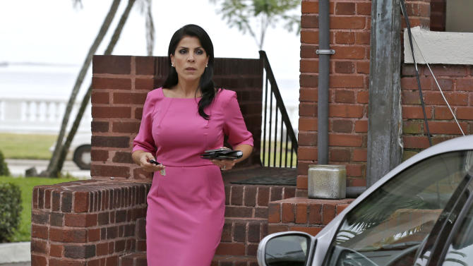 Jill Kelley leaves her home Tuesday, Nov 13, 2012 in Tampa, Fla. Kelley is identified as the woman who allegedly received harassing emails from Gen. David Petraeus' paramour, Paula Broadwell. She serves as an unpaid social liaison to MacDill Air Force Base in Tampa, where the military's Central Command and Special Operations Command are located. (AP Photo/Chris O'Meara)