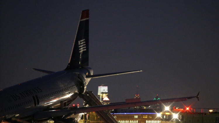 Investigators work near a damaged US Airways jet at the end of a runway at the Philadelphia International Airport, Thursday, March 13, 2014, in Philadelphia. Airline officials said the flight was heading to Fort Lauderdale, Fla., when the pilot was forced to abort takeoff around 6:30 p.m., after the front landing gear failed. An airport spokeswoman said no injuries have been reported. (AP Photo/Matt Slocum)