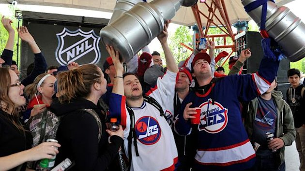 Hockey fans celebrate the return of NHL hockey during a rally in Winnipeg, Manitoba, May 31, 2011. Canada reclaimed one of its lost NHL franchises on Tuesday when the Atlanta Thrashers were sold to True North Sports and Entertainment and relocated to Winn