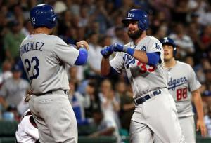Dodgers batter Van Slyke celebrates with team mates as he crosses home-plate after hitting a home run against the Diamondbacks during opening game of 2014 MLB season