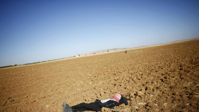 Syrian Kurdish refugee sleeps on the ground on the Turkish-Syrian border near town of Suruc in Sanliurfa province