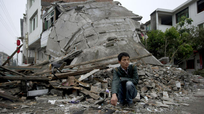 AP10ThingsToSee - A man squats near the collapsed remains of a building destroyed by an earthquake in Lushan county in southwestern China's Sichuan province, Monday, April 22, 2013. (AP Photo/Ng Han Guan, File)