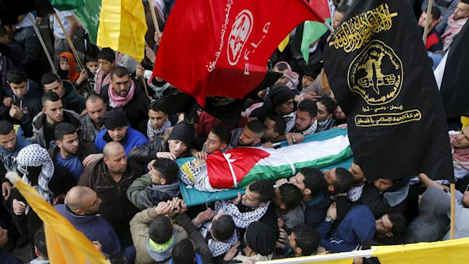 Mourners carry the body of Palestinian youth Omar Madi, who was shot and killed by Israeli troops on Wednesday, during his funeral in Arroub refugee camp, north of Hebron