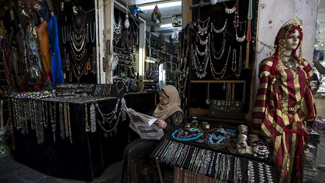 A shopkeeper reads a newspaper as she waits for customers at the Medina of Tunis